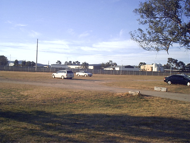 The view looking looking from the racecourse carpark. The platform location is approximately behind the far white car. Racegoers would have walked across to the meetings. In the background are the warehouses of the North Albury industrial estate.