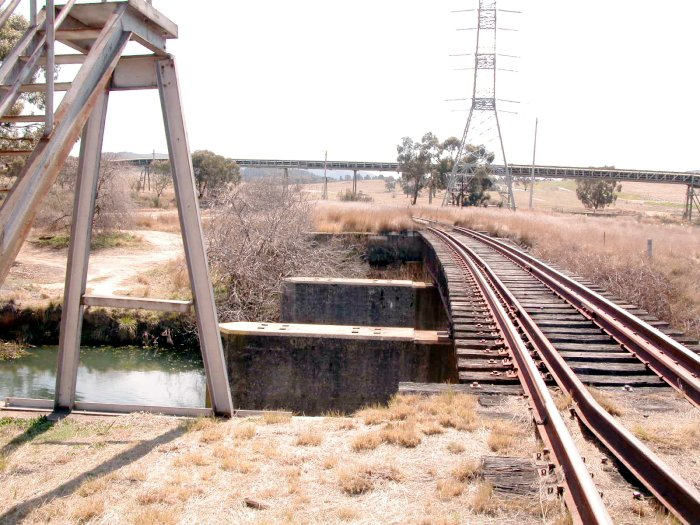 The view looking north from the north junction.  The bridge over the creek was clearly constructed for double tracks. The elevated structure is a coal conveyor belt.