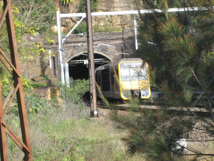 A Hornsby-bound Tangara set exits the northern portal of the Bay Road Tunnel.