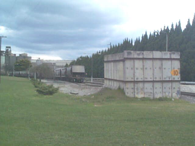 A closer view of the tail end of a train in the cement works, and one of the unusual concrete structures at the entrance to the yard.