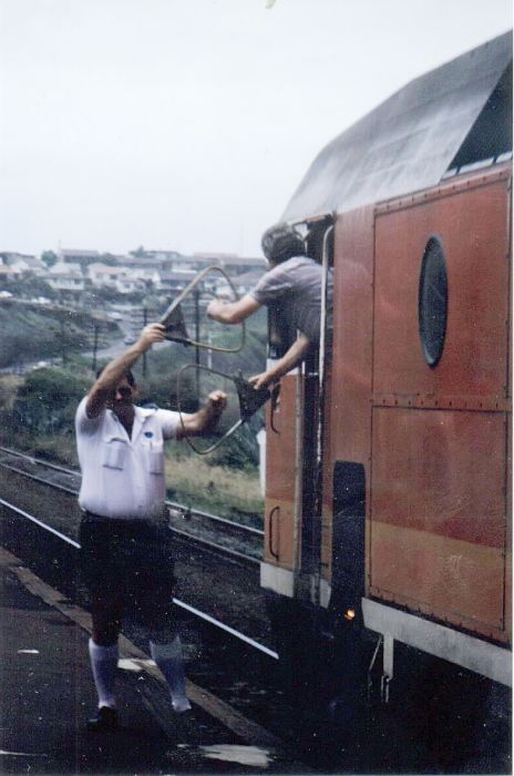 An integral part of single line rail operation was the exchanging of the staff at a safeworking point. A classic pose is shown here at Bombo in 1986 as the up South Coast Daylight slowly trundles through.