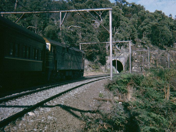 An unidentified 442-class loco hauls a passenger train up Cowan Bank past the portal of the abandoned Boronia No 5 Tunnel.