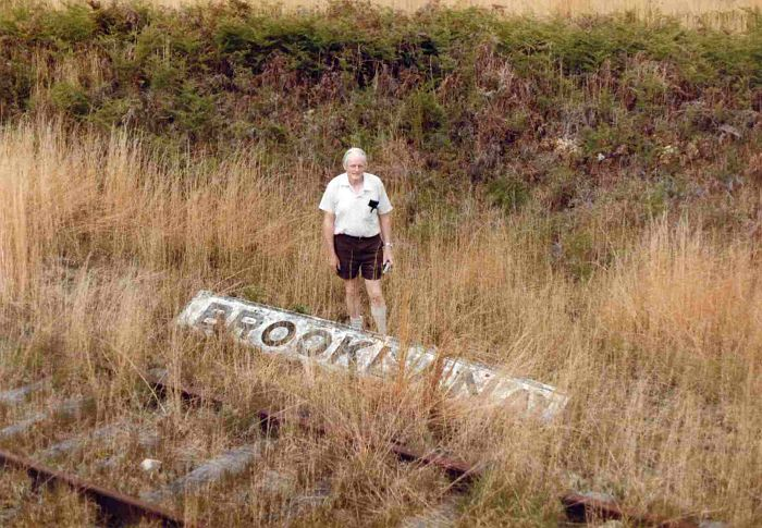 The old station name-board, lying in the grass next to the track.