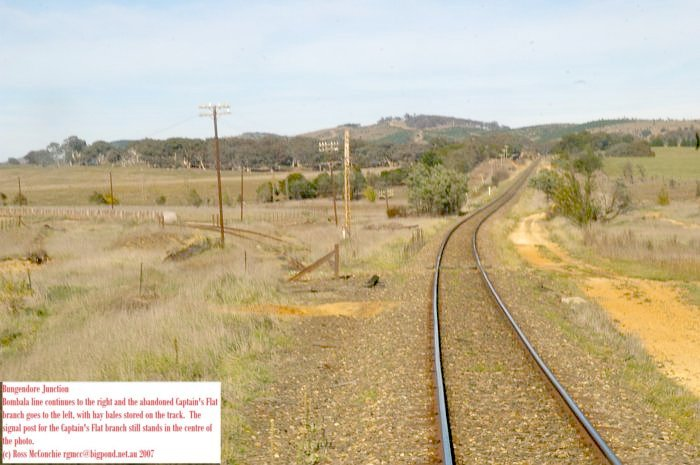 The Bombala line continues to the right and the abandoned Captains Flat branch goes to the left, with hay bales stored on the track. The signal post for the Captains Flat branch still stands in the centre of the photo.