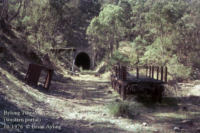 Remains of abandoned construction equipment outside the western portal of Bylong Tunnel in 1976. The bore was incomplete and flooded, blocking access.