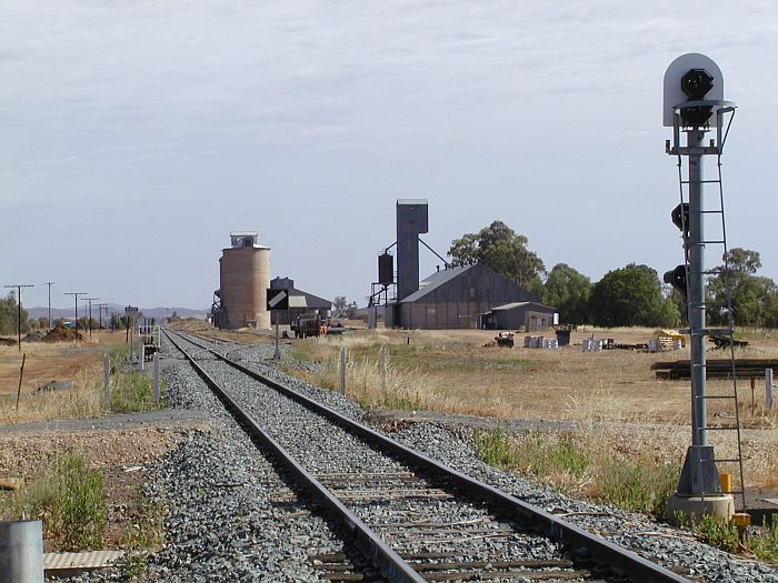 The view looking north from the level crossing where the Mid-Western Highway crosses the line.  There are men working on the siding to the silos.