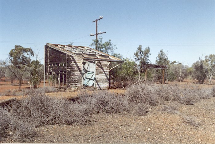 A view looking across at the burnt-out station building, still featuring its name board.