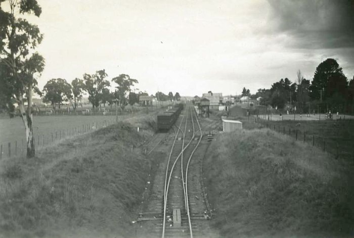 The view looking down the line towards the station. A set of stock wagons are visible in the sidingon the left. On the right of the line can be seen the elevated water tank and the station building beyond.