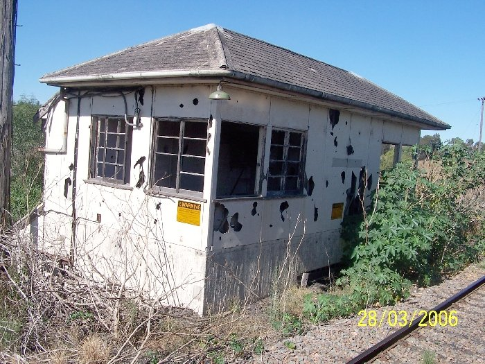 A closer view of the old Newdell Signal Box, showing its dilapidated state and asbestos warning signs.