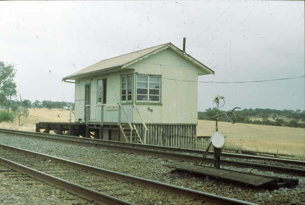 "Kapooka Signal Box sat off the main road and was rather an isolated box but was an important crossing point. This 1980 photo shows an automatic staff exchanger ready for an up train to Wagga. The staff was placed in the top ring for collection by the locomotive while the bottom ""rams horn"" took the staff from the Uranquinty section, all at speed."