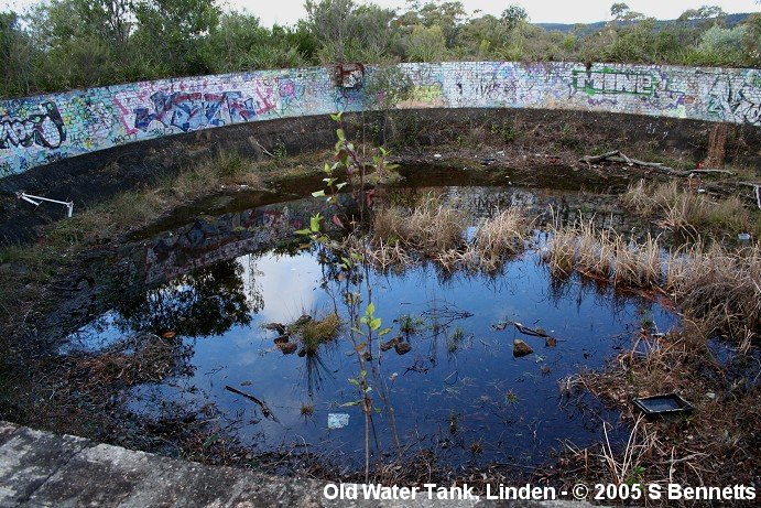 A photo of an old water tank at Linden. It is located in overgrown bush between the Down Main and the Great Western Highway. There is almost no noticable sign of its existence of location from either the highway or the railway. This view shows the south and western sides of the tank, the hills seen forming the horizon on the right of the photo are the eastern side of the ridge running north-south known as the Woodford Bends.  Acording to the ARHS Bulletin no. 241 - Nov 1957 a water tank was built in 1885 and on the diagrams illustrating the article the location shown is very close to where the Brick sided concrete lined tank in the photo is found today.