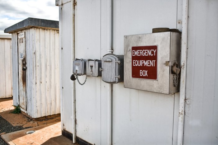 Telephone and emergency equipment mounted outside one of the huts at the location.