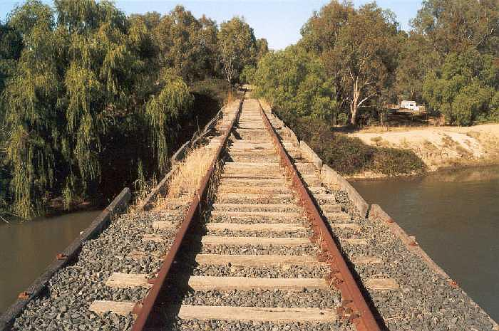 The view looking south of the bridge over the Murrumbidgee Northern Canal showing the deteriorating ballasted decking.