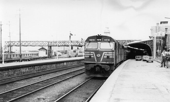 44230 sits at the head of a passenger train bound for Sydney.  At the left is the part of the extensive goods yard, now long gone.