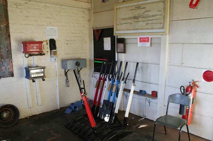 The interior of the signal box, showing the staff boxes, lever frame and yard diagram. The Nyngan-Cobar staff is missing, indicating that a train is in that section.