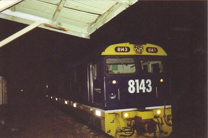 8143 heads west through the station at night.