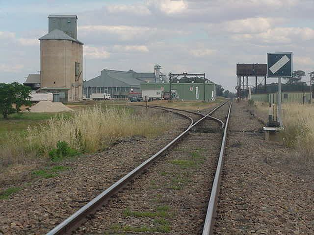 The view looking south to the silo siding.  Note the presence of the gantry crane and large elevated water tank.  The station was located just beyond the tank, on the same side of the line.