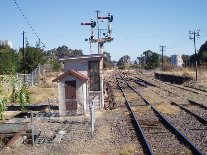 The view looking down the line beyond the station. The small cabin encloses the F Frame. The signals control the former main line to Bombala (left) and the branch line to Canberra (right). On the far right is the remains of the stock loading platform.