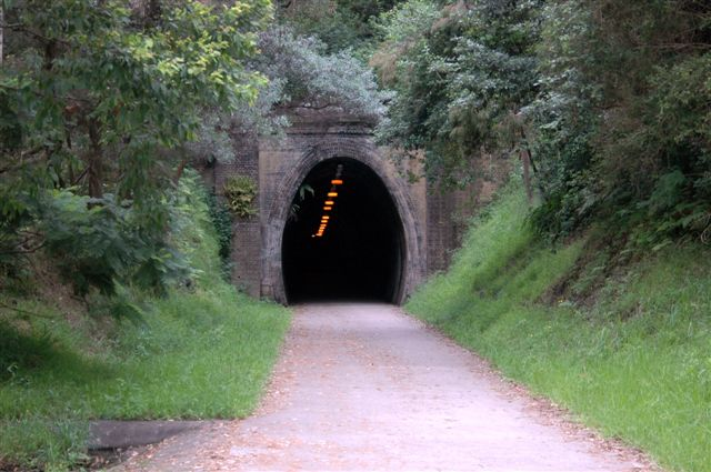 The up portal. The track bed has been converted into a rail trail, with lighting provided in the tunnel.