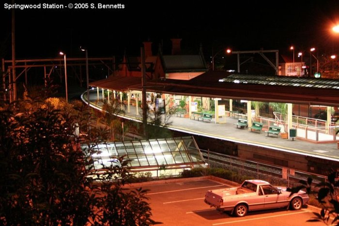 A photo of Springwood station taken after dark from the top level of the multi storey commuter carpark, looking down at Up main and platform 1.