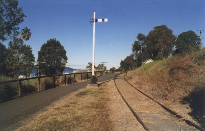 The up home signal at the approaches to Toronto station.  Lake Macquarie is visible between the trees on the left.