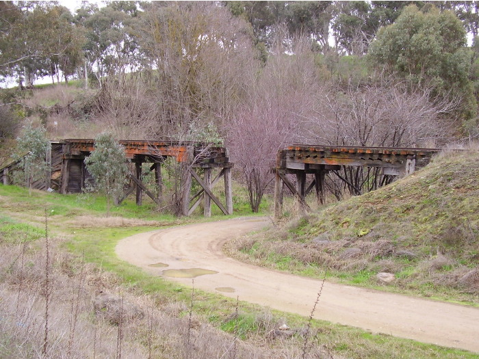 For part of the way the Tumut Branch Line runs parallel to the Snowy Mountains Highway.  This timber bridge, now cut in the middle, is located next to the highway about 10 kilometres west of Tumut; the view being of the southern side of the bridge.