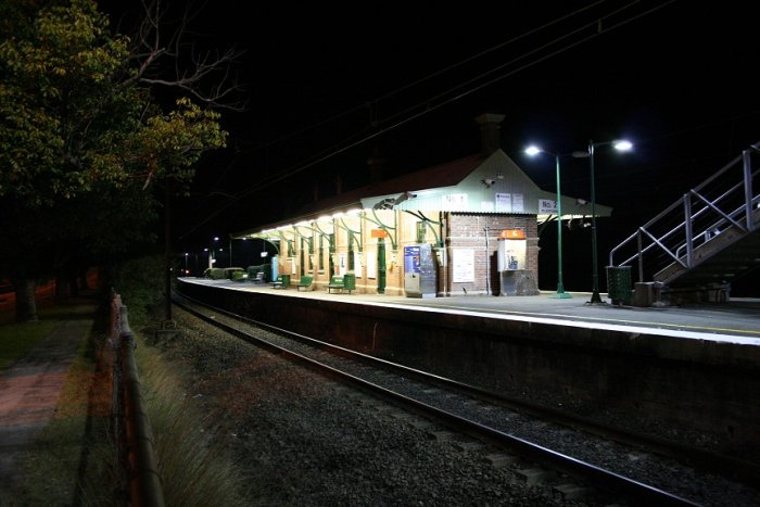 A photo taken after dark from under the footbridge over the highway on the Up side of Valley Heights station. Photo is taken looking towards Sydney showing the Up main and Platform 1.
