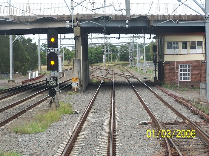Woodville Junction Signal Box sits beneath Donald Street bridge and is completely invisible from the roadway above. The junction is visible in the background:  straight ahead the line curves  to the right to Hamilton and Newcastle, with a turnout to the left towards Islington Junction and further on to Maitland.
