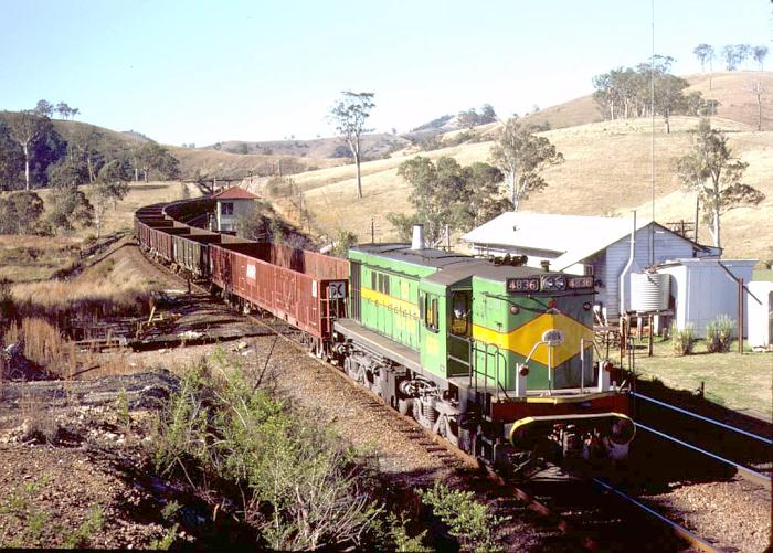 4836 heads south with a load of empty open wagons through the one-time crossing loop at Yumbunga.